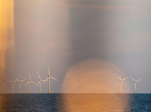 Wind turbines in the sea against sunset